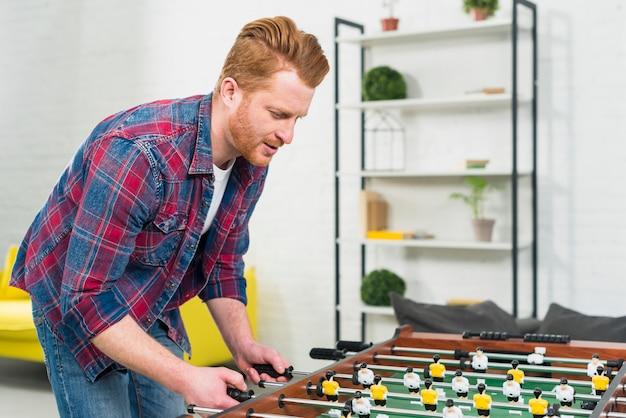 若い男が自宅でサッカーテーブルサッカーゲームをプレイのクローズアップ 無料写真