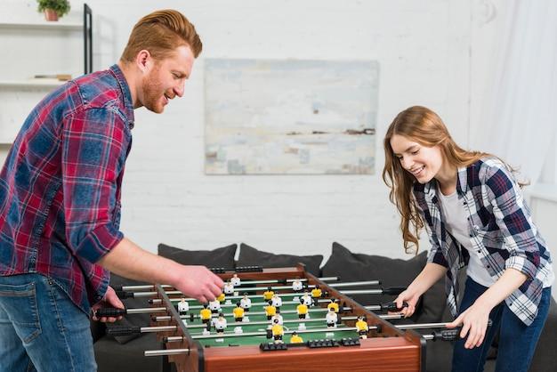 幸せな若いカップルが自宅でサッカーテーブルサッカーゲームをプレイ 無料写真