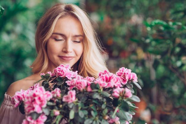 ピンクの花の臭いがする若いブロンドの女性の肖像画 無料写真
