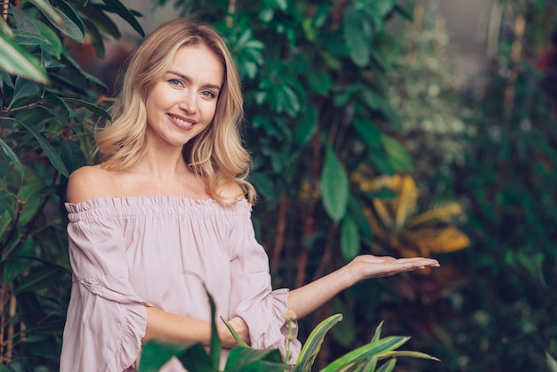 提示する庭に立っている笑顔金髪の若い女性の肖像画 無料写真