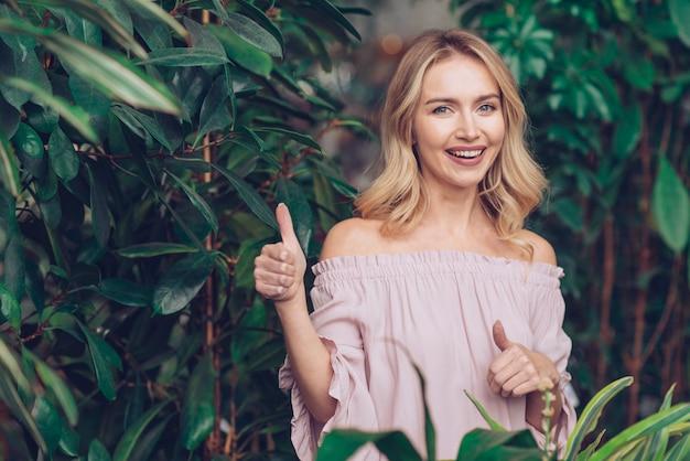 今すぐ登録親指を示す緑の植物の近くに立って幸せな金髪の若い女 無料写真