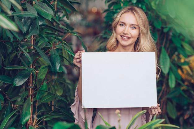 白い空白プラカードを示す植物保育園に立っている笑顔金髪の若い女性の肖像画 無料写真