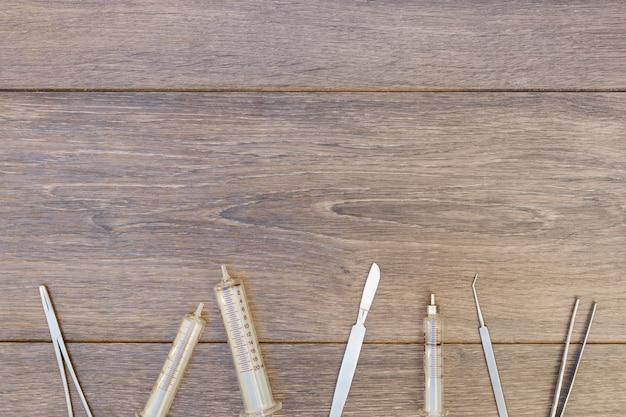空のプラスチック注射器と木製の机の上の手術器具 無料写真