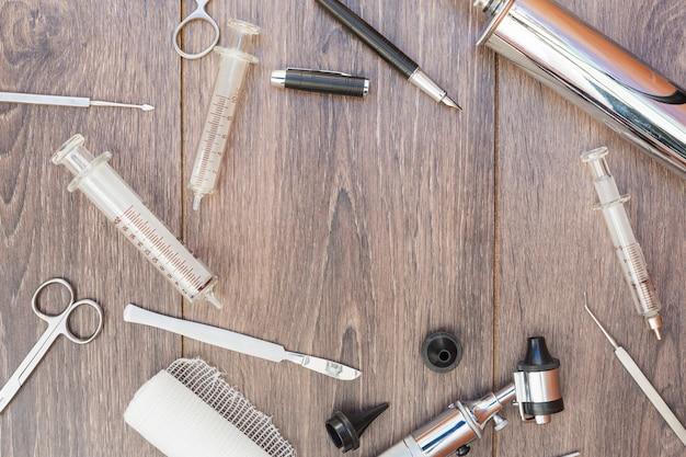 耳鏡シリンジ手術器具ロールガーゼと木製の机の上の黒い万年筆 無料写真