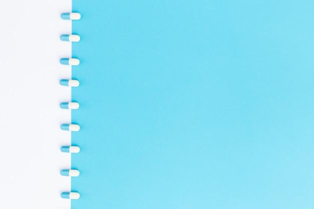 白と青のデュアル背景にカプセルの行 無料写真