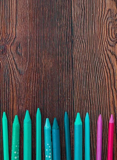 木製の背景の下部に配置されたカラフルなクレヨン 無料写真