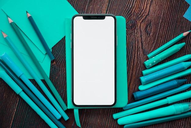 Мобильный телефон с белым экраном на дневнике возле картины цвета над деревянным столом Бесплатные Фотографии