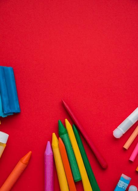 粘土と接着剤の鮮やかな赤い背景の上にカラフルなクレヨン 無料写真