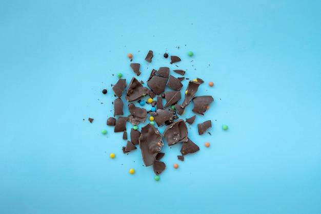 青いテーブルの上の小さなキャンディーとひびの入ったチョコレート 無料写真