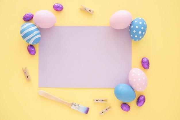 黄色のテーブルに空白の紫紙とイースターエッグ 無料写真