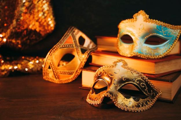木製の机の上の本を持つ女性のカーニバルマスクのクローズアップ 無料写真
