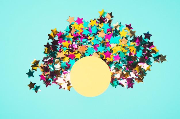 Круглая желтая рамка в окружении красочных звездных конфетти на синем фоне Бесплатные Фотографии