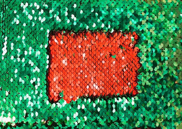 ダークグリッターグリーンの反射スパンコールの内側に赤いスパンコール 無料写真