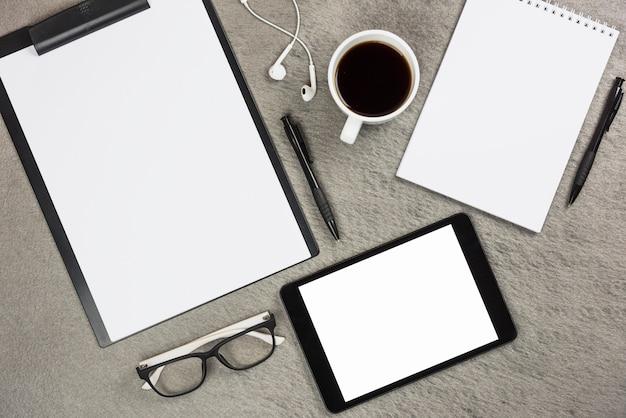 Вид сверху канцелярских принадлежностей с чашкой кофе и цифровой планшет на сером столе Бесплатные Фотографии