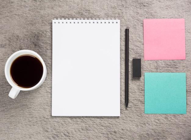コーヒーカップ;空白のスパイラルメモ帳。黒消しゴム灰色の机の上の鉛筆と粘着メモ 無料写真