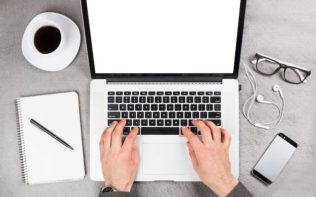 Крупный план руки бизнесмена, набрав на цифровой планшет с канцелярских принадлежностей и чашка кофе на столе Бесплатные Фотографии