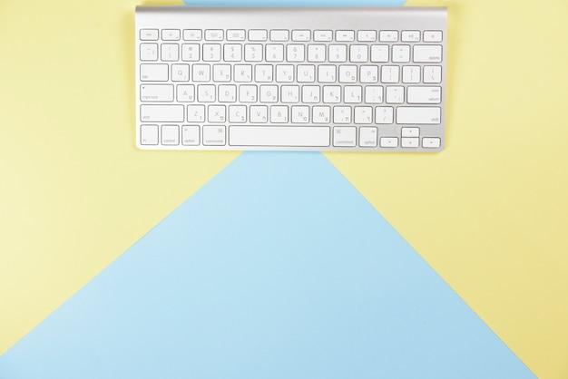 黄色と青の背景にワイヤレスの白いキーボード 無料写真