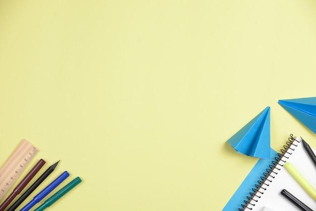 テキストを書くためのスペースを持つ黄色の背景に対してオフィス文房具で青い紙を折り 無料写真