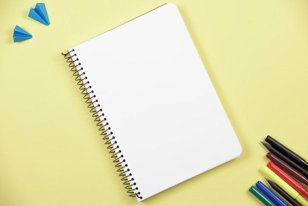 黄色の背景にカラフルなフェルトペンで空白のスパイラルノート 無料写真