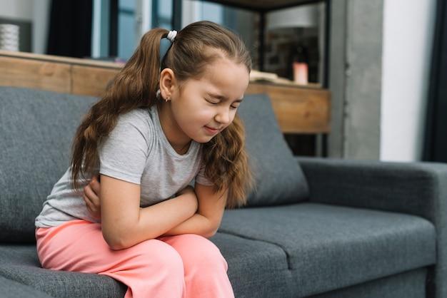 Маленькая девочка держит руки на животе страдает от боли Бесплатные Фотографии
