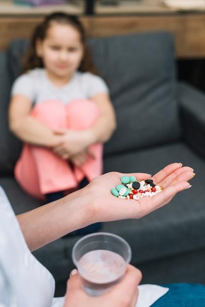 ソファの上に座っている女の子の前に別の薬と一緒に女医の手のクローズアップ 無料写真