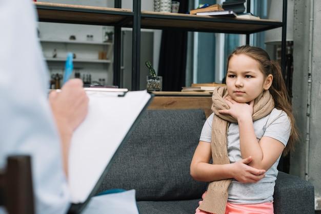 Больная девушка с шарфом на шее сидит перед женщиной, пишет в буфер обмена с ручкой Бесплатные Фотографии