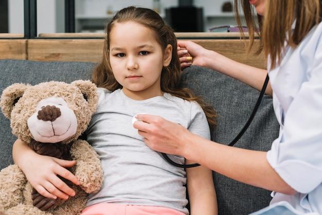 Рука женского доктора рассматривая больную девушку держа плюшевого медвежонка с стетоскопом Бесплатные Фотографии