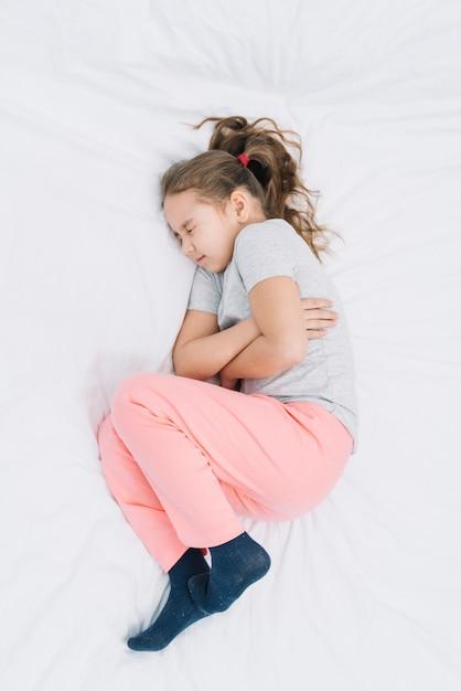 胃の痛みを持って靴下を履いて病気の女の子の立面図 無料写真
