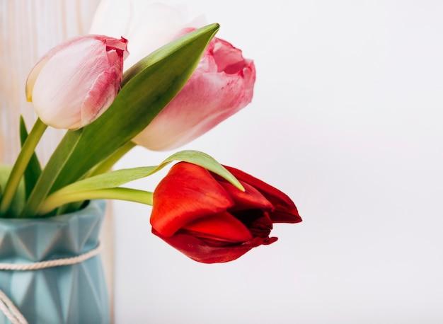 白い背景の上の花瓶に新鮮なチューリップの花のクローズアップ 無料写真