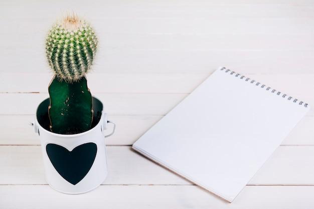 木製の机の上の空白のスパイラルメモ帳の近くのカップのサボテンの植物 無料写真