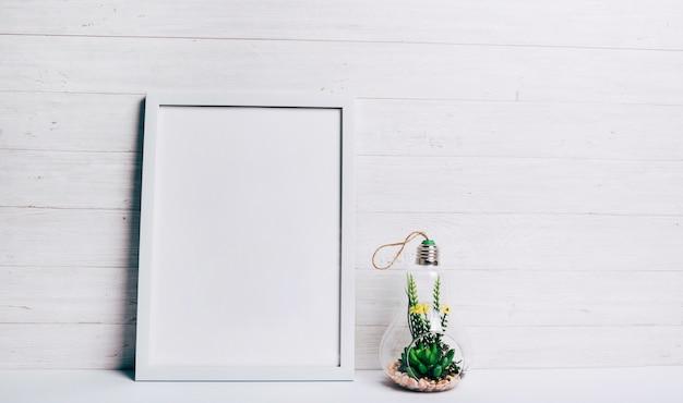 Миниатюрное суккулентное растение внутри стеклянной подвесной лампы возле белой рамки у деревянной стены Бесплатные Фотографии