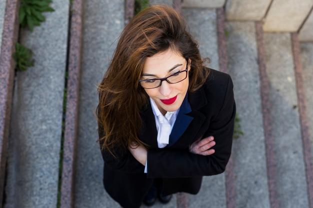 Деловая женщина в черном костюме стоит на лестнице снаружи Бесплатные Фотографии