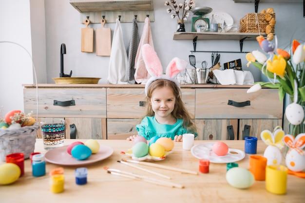 イースターエッグとテーブルに座っているバニーの耳でかわいい女の子 無料写真