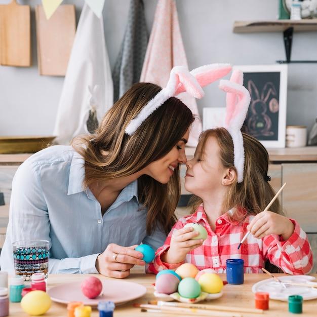 イースターのための卵を塗っている間小さな女の子と母親の鼻に触れる 無料写真