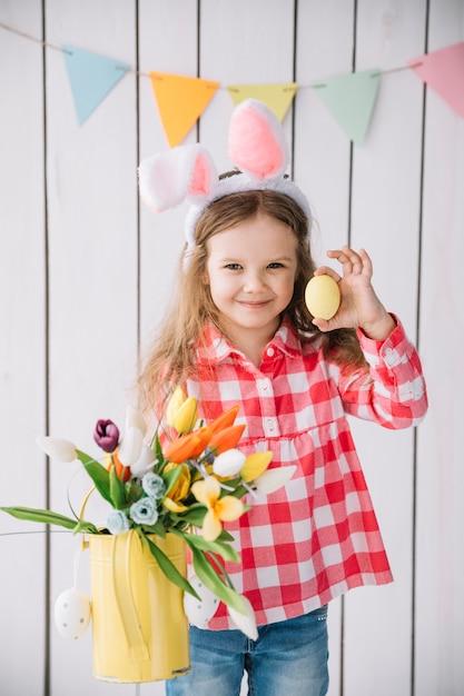 水まき缶でイースターエッグと花を保持しているバニーの耳の女の子 無料写真