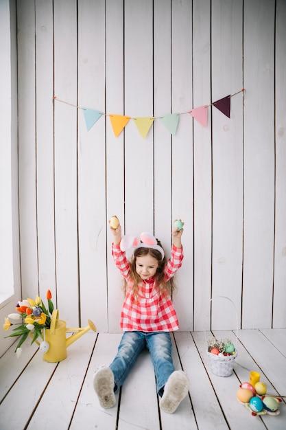 手でイースターの卵を保持しているバニーの耳でかわいい女の子 無料写真