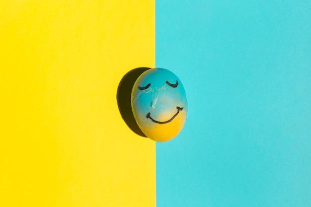 テーブルの上の塗装の笑顔とイースターエッグ 無料写真