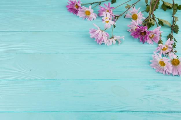 明るい花が青い木製のテーブルに散らばって 無料写真