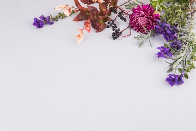 テーブルの上の植物の枝と明るい花 無料写真