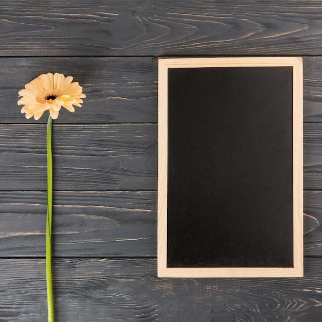 テーブルの上の空白の黒板とオレンジのガーベラの花 無料写真