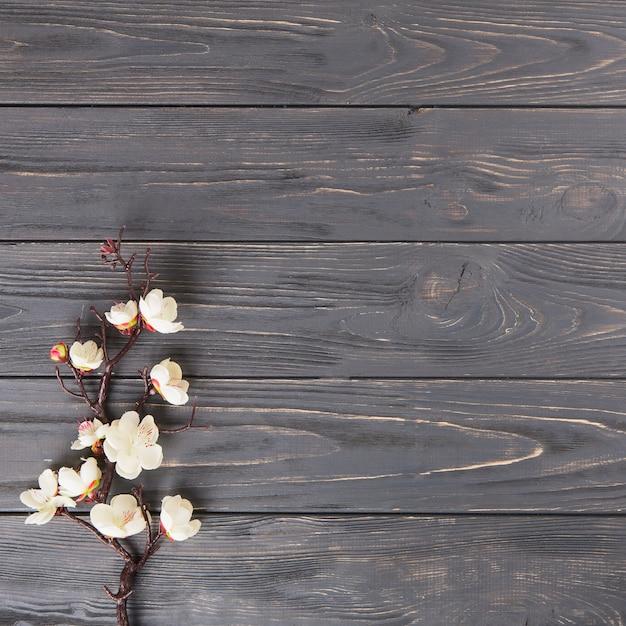 木製のテーブルの上の白い花と木の枝 無料写真