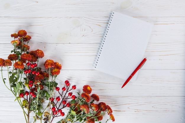 空白のノートブックと木製のテーブルの上にペンで赤い花 無料写真