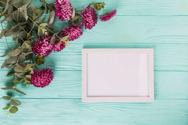 青い木製のテーブルの上の空白のフレームと紫の花 無料写真