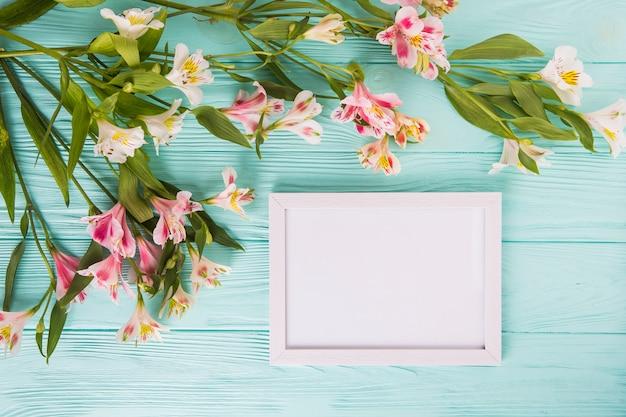 テーブルの上の空白のフレームとピンクの花 無料写真