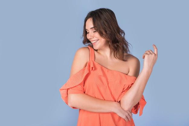 オレンジ色のブラウスでエレガントな女性を笑顔 無料写真