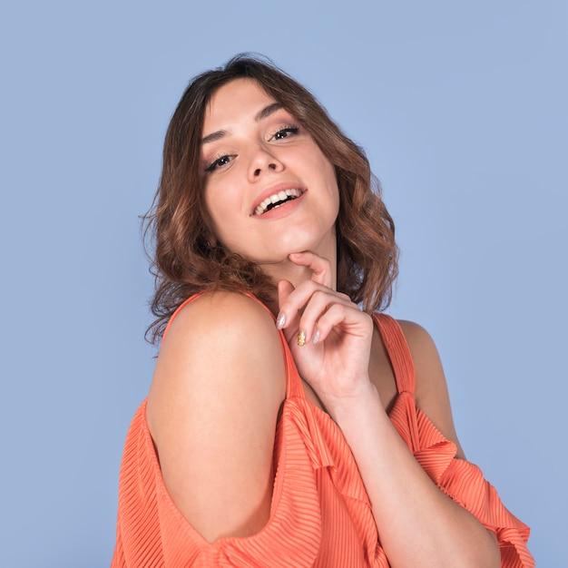 あごを保持しているブラウスの情熱的な女性の笑みを浮かべてください。 無料写真