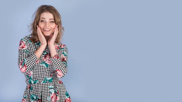 顔に手を持つエレガントなドレスで幸せな若い女 無料写真
