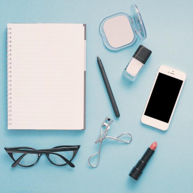 ノートブックと青いテーブルの上の化粧品のスマートフォン 無料写真