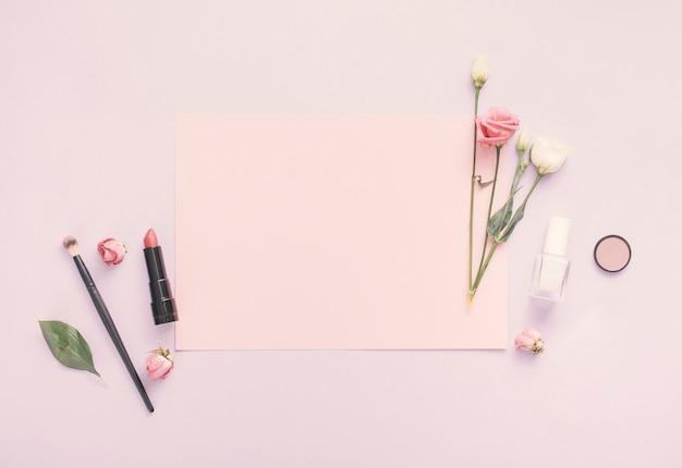 白紙の紙、花、マニキュア、テーブルの上の口紅 無料写真