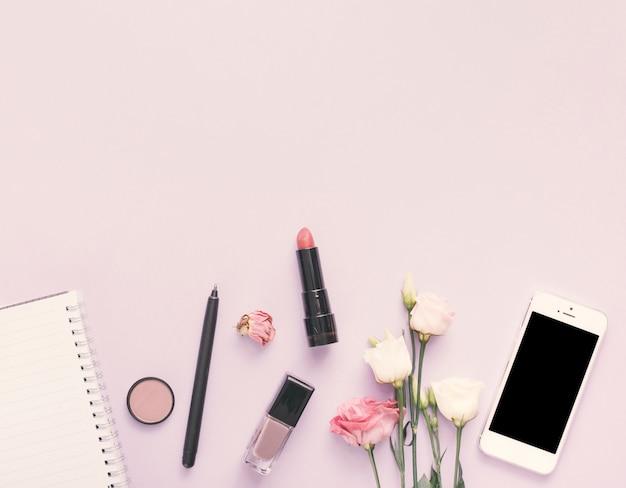 スマートフォン、花と化粧品ライトテーブルの上のノート 無料写真